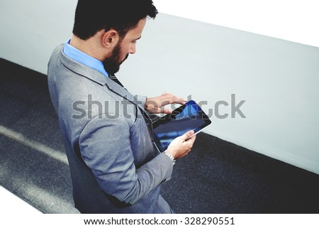 Top view of a purposeful intelligent lawyer man holding touch pad with copy space screen for your promotional content, young male skilled manager in luxury suit using digital tablet in modern office - stock photo