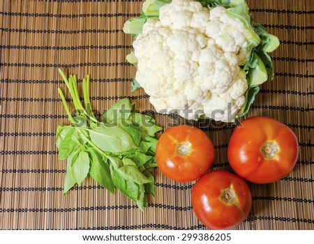 Top view of a raw cauliflower vegetable, three tomatoes and a bunch of fresh organic basil on a rustic bamboo tablecloth - stock photo