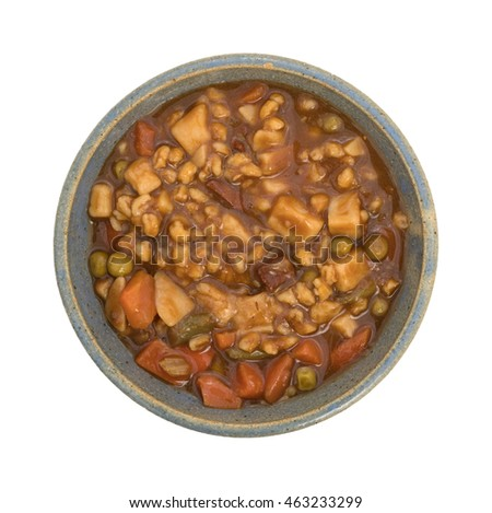 Top view of a serving of canned beef stew in an old bowl on a white background.