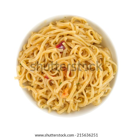 Top view of a serving of Chow Mein noodles with shrimp and seasonings in a small bowl isolated on a white background.