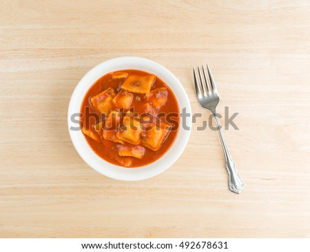 Top view of a serving of ravioli in a white bowl on a wood table with a fork to the side.