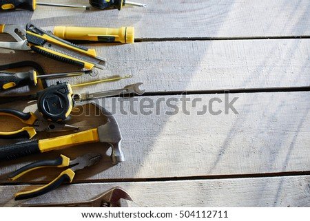 Top view of a set of tools lying on a table of wooden planks