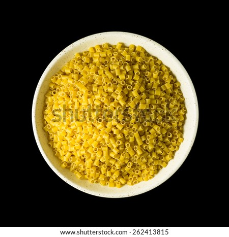 Top view of a shallow bowl filled with ditalini pasta on a black background. - stock photo