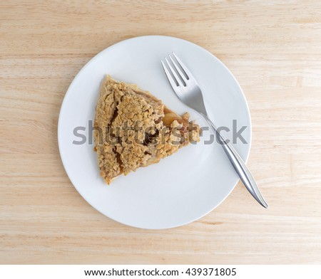 Top view of a slice of Dutch apple pie on a plate with a fork to the side atop a wood table top.