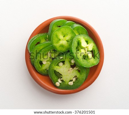 Top view of a small bowl of sliced jalapeno peppers on an off white tablecloth illuminated with natural light. - stock photo
