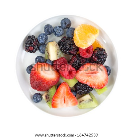 Top view of a small bowl with blueberries, red and black raspberries, kiwi, cut strawberries and an orange slice.