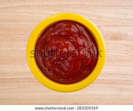 Top view of a small colorful yellow portion bowl filled with ketchup on a wood counter top. - stock photo