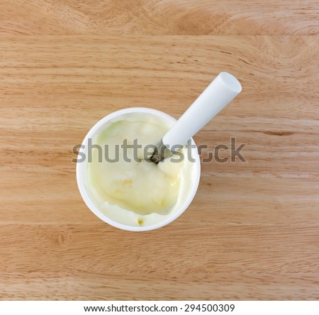 Top view of a small container of pineapple yogurt with a white handle spoon on a wood table top. - stock photo