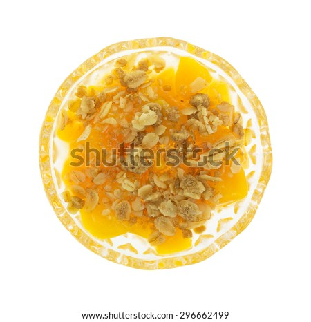 Top view of a small glass bowl of diced peaches in heavy syrup with oats and brown sugar topping isolated on a white background. - stock photo