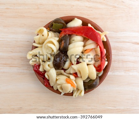 Top view of a small serving of rotini pasta salad in a small bowl isolated on a wood table top. - stock photo