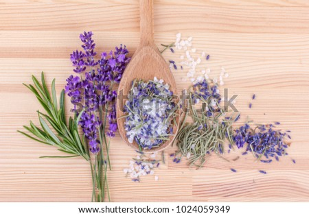 top view of a spoon with herbal salt of rosemary and lavender blossoms on a wooden background