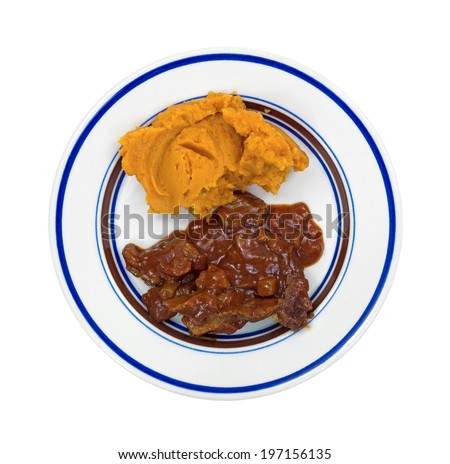 Top view of a sweet potato and braised beef in a hot sauce TV dinner on a small plate. - stock photo