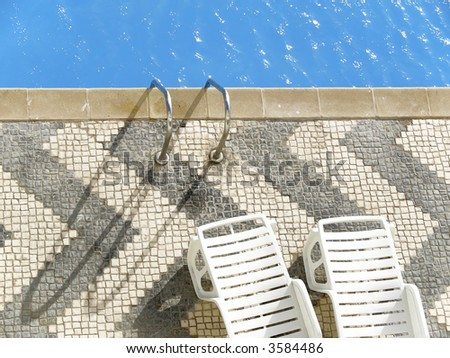 Top view of a swimming pool with two empty white deckchairs. - stock photo