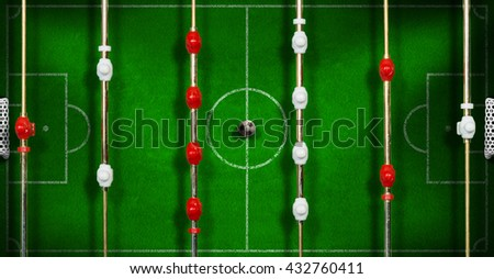 Top view of a table football game with an old black and white soccer ball - stock photo