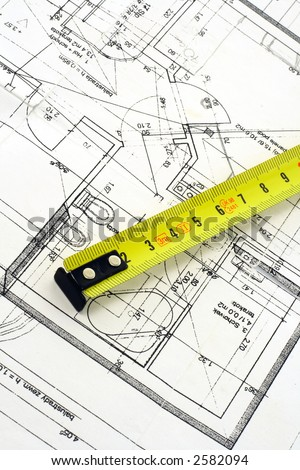 Top view of a tape measure on top of floor plan - stock photo