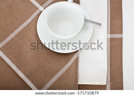 top view of a tea Cup and saucer on a brown tablecloth