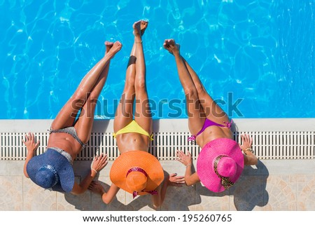 Top view of a  three girls by the swimming pool - stock photo