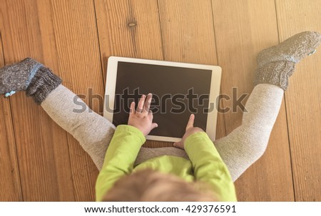 top view of a toddler in green shirt playing with a tablet device on a wooden floor - stock photo