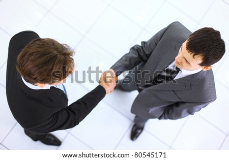 Top view of a two businessman shaking hands - Welcome to business - stock photo