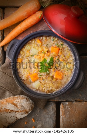 Top view of a warm and delicious freshly made pot of soup with raw carrots, chickpeas and a loaf of rustic bread - stock photo