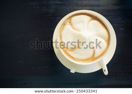Top view of a white cup of hot cappuccino coffee with white spoon on white saucer, isolate on white over grunge wood - stock photo