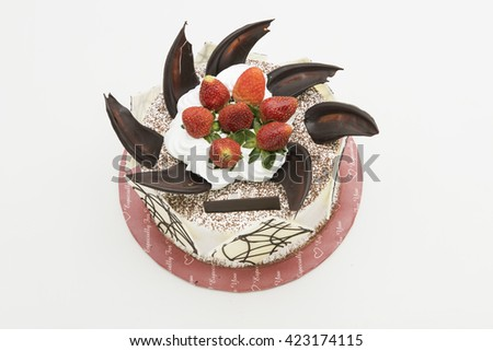 Top view of a whole cake with topping of fresh strawberry fruits on white cream, sprinkle with cocoa powder and decorated with chocolate shards and sheets.  Isolated on white background. - stock photo