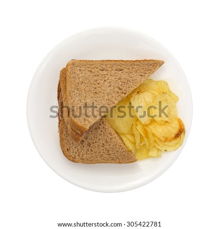 Top view of a whole wheat sandwich with potato chips on a white plate.