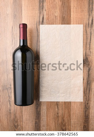 Top view of a wine bottle next to a blank sheet of paper. Wine list concept. - stock photo