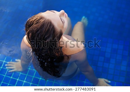 top view of a woman sitting in a swimming pool in the evening - stock photo