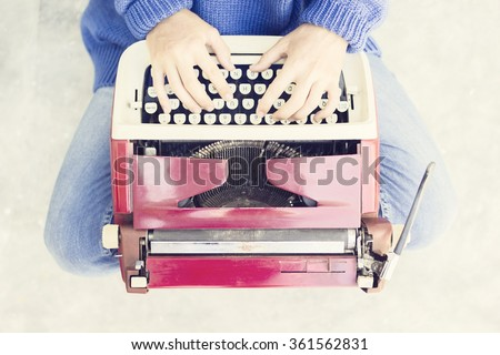 Top view of a woman sitting on the floor and typing typewriter - stock photo