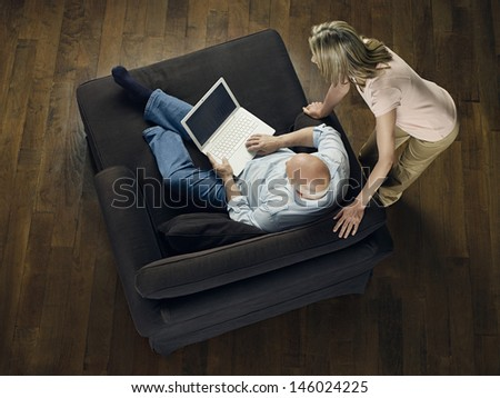 Top view of a woman watching mature bald man use laptop on sofa at home - stock photo