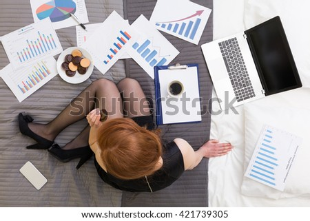 Top view of a woman working and eating on a bed