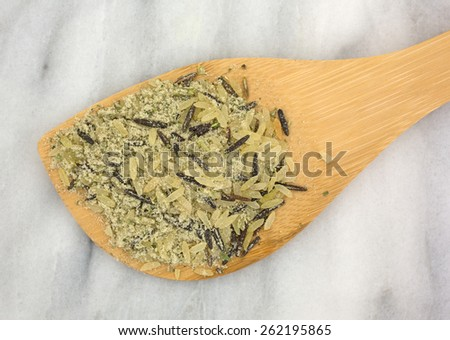 Top view of a wood spoon atop a marble cutting board with a portion of long grain wild rice and seasonings. - stock photo