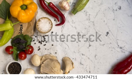Top view of a yellow bell pepper, red chili peppers, green peppers, cherry tomatoes, basil leaves, mushrooms, courgettes, black peppercorns and salt on a white marble background with copy space. - stock photo
