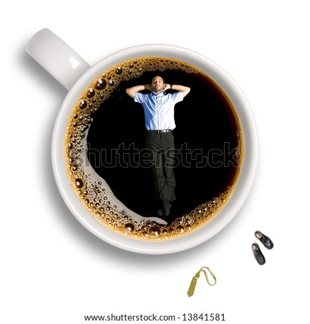 Top view of a young business man taking a nap inside an isolated cup of coffee with his tie and shoes sitting aside.