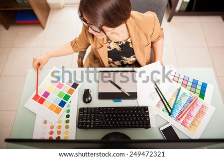Top view of a young graphic designer working on a desktop computer and using some color swatches - stock photo