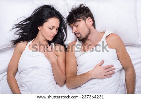 Top view of a young happy couple are sleeping in bed.