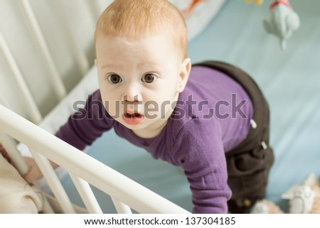 Top view of adorable baby boy trying to stand up in his cot - stock photo