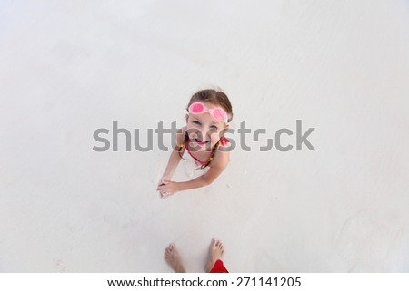Top view of adorable little girl at beach during summer vacation - stock photo