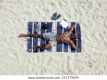 Top view of afro american young man relaxing on beach. Muscular guy wearing sunglasses and listening to music on headphones lying on a beach mat. Shirtless male model sunbathing. - stock photo