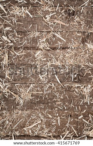 Top View of Aged, Rough textured Rustic dark Brown Cedar Wood Boards with hay scattered for Backgrounds and Templates with Blank Room or Space for your Design, Words, Text or Copy. Vertical