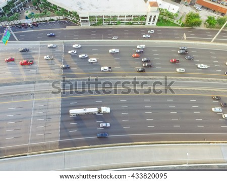 Top view of an asphalt elevated highway in Houston, Texas, US. Many passenger cars and trucks are commuting in freeway at late afternoon with warm light. Great for urban transportation publication.