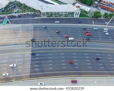 Top view of an asphalt elevated highway in Houston, Texas, US. Many passenger cars and trucks are commuting in freeway at late afternoon with warm light. Great for urban transportation publication. - stock photo