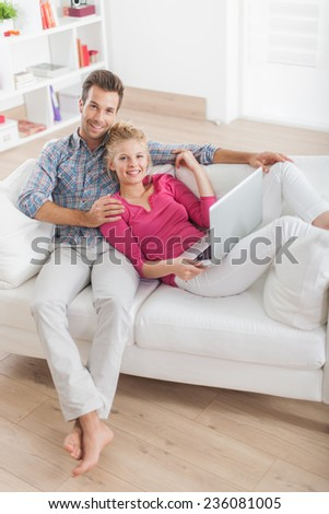 Top view of an handsome couple relaxing barefoot on a white sofa and using laptop