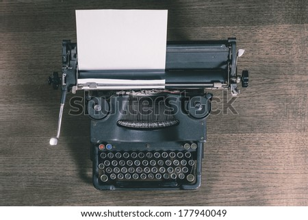 Top view of an old typewriter on a wooden table, photo in retro style