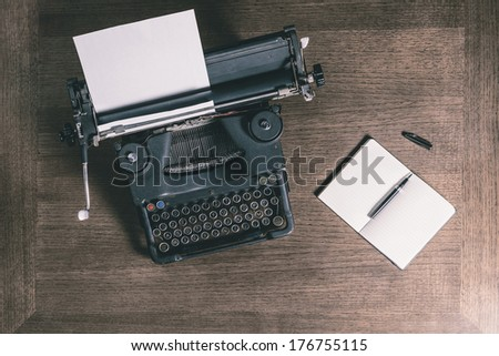 Top view of an old typewriter with a pen and a notebook on a wooden table, photo in retro style - stock photo