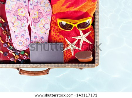 top view of an open suitcase with full of summer stuff on blue background - stock photo