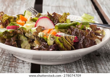 Top view of an organic Italian chopped green garden salad on an old barn wood table - stock photo