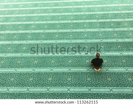 Top view of an unidentified Muslim man prays in a mosque - stock photo