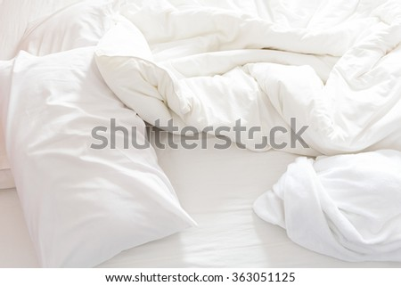 Top view of an unmade bed after waking up in the morning. White pillows, a blanket and a shower towel are on the bed. - stock photo